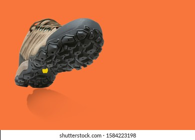 sports shoe as if striding on an orange surface, casting a shadow, the concept of shoes for an active lifestyle, copy space
