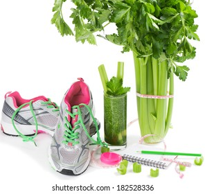 Sports shoes, notebook, pencil and fresh celery, glass with juice isolated on white. Planning of a diet.
