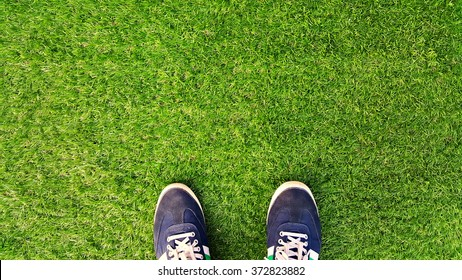 Sports shoes on artificial grass .