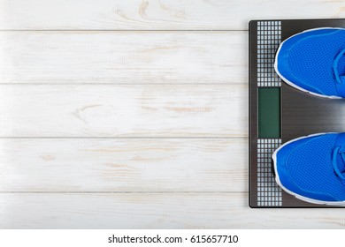 Sports shoes standing on the scales on white wood background. Concept plan.