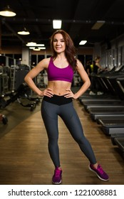 Sports, slender girl standing on the background of exercise machines and treadmills in sportswear.