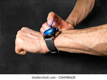 Sports smart watch on the athlete's hand on the background of chalk drawing Board