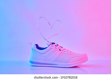 Sports sneakers with heart-shaped laces in neon light. Concept of Love and Valentine's Day.