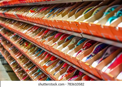 a lot of sports sneakers in the orange paper boxes on shelf, ready to sales.