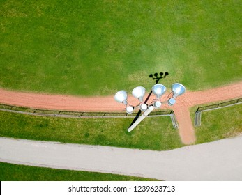 Sports soccer and football with nice green environment, aerial view behind stadium lights or lamps. Recreational activity  ground in top view of field in neighbourhood at sunny hot summer day.
