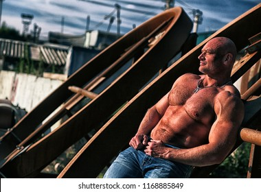 sports, tanned man on the background of an industrial landscape