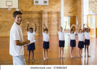 Sports teacher writing notes on clipboard while students exercising in school gym