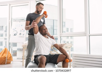 Sports therapy. Pleasant good looking man exercising with dumbbells while being in the gym