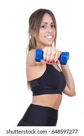 Sports training. Beautiful young woman in sports clothing training with dumbbells and smiling while standing isolated on white background.