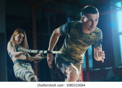 Sports training couple in the gym. Young man and woman doing exercise with rope trx system. Man pulls the ropes and woman holds her. Workout.