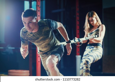 Sports training couple in the gym. Young man and woman doing exercise with rope. Man pulls the ropes and woman trainer holds her. Workout.