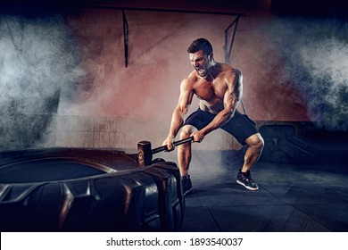 Sports training for endurance, man hits hammer. Concept workout.