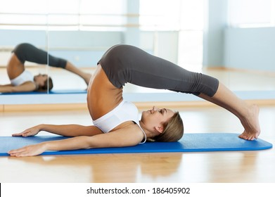 Sports training. Side view of beautiful young woman training on yoga mat