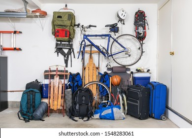 Sports and travel gear and equipment in piles in corner of messy suburban garage.