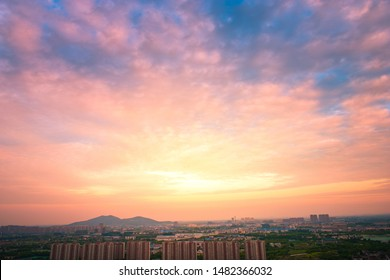 Sports virtual asphalt roads, road lines, roadside greening trees, distant cities and mountains, evening full of red color sunset