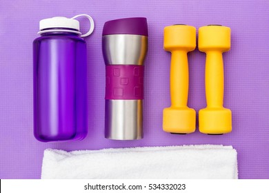 sports ware for gym. Sport concept. Sporting items on purple background or lavender. White towel, yellow dumbbells, bottle of water, a jar of food. Sports nutrition.