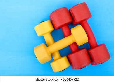 sports ware for gym. Sport concept. Sporting items on blue background or lavender. Yellow  and red dumbbell on purple mat sport. Space for your text. Sports concept. Sport equipment. Fitness
