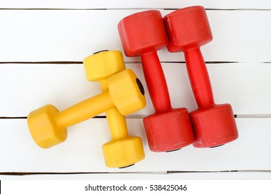sports ware for gym. Sport concept. Sporting items on white boards. Yellow and red dumbbell on purple mat sport. Space for your text. Sports concept. Sport equipment. Fitness