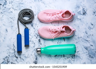 Sports water bottle, shoes and jumping rope on light background