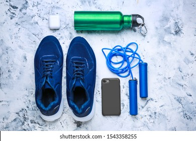 Sports water bottle, shoes, mobile phone and jumping rope on light background