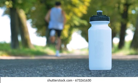 A sports white bottle (shaker) for drinking stands on the asphalt, the background runs through a man on the street. Concept: love sports, healthy lifestyle, be beautiful, muscles, happy, burn calories