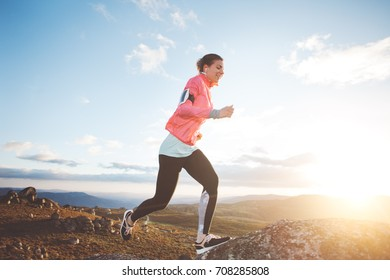 Sports womam running in the mountains at sunset against the backdrop of a beautiful landscape. Sport tight clothes. Intentional motion blur.