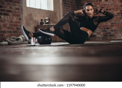 Sports woman doing bicycle crunch workout at gym. Female in the gym doing abs workout exercise at fitness club.