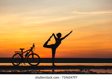 The sports woman doing yoga at sunrise on the sea beach against the background of orange sky and bicycle. Fitness concept.