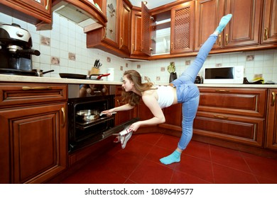 Sports woman in the kitchen, she cooks food and does exercises.