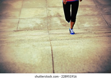 sports woman legs running up on stone stairs