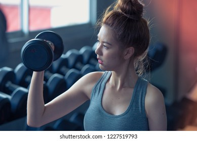 Sports woman lifting weights in the sport gym ,bodybuilding and loose weight concept.
