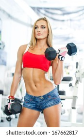 Sports woman. Woman lifting weights in a training session