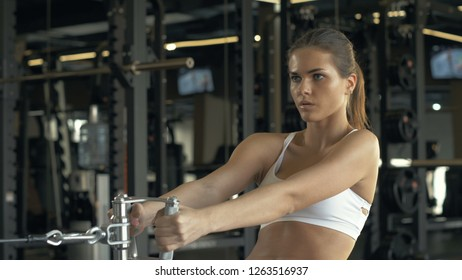 Sports woman pulling weight on fitnes equipment in sports club interior