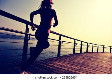 sports woman running on wooden boardwalk sunrise seaside