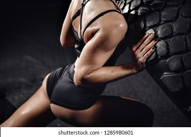 Sports woman in shorts turns over tire wheel in gym, sweat drops, force. Fitness workout concept.