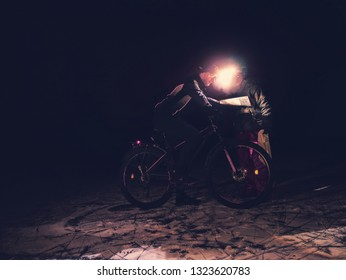 Sports woman shows position in paper map, man biker trace her finger with headlamp light. Cold winter night.