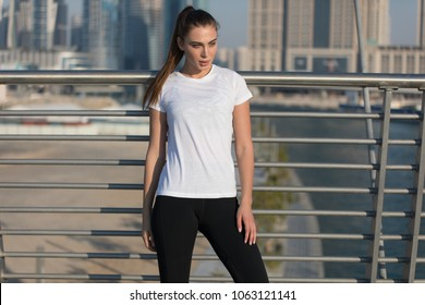 Sports woman in a white T-shirt while training on the bridge. Mock-up.