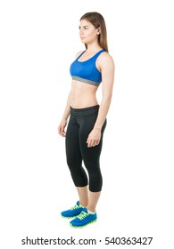 Sports young girl in the form of (a sports bra and shorts) and sneakers  stands sideways on a white background. Healthy lifestyle. Mock up. Human