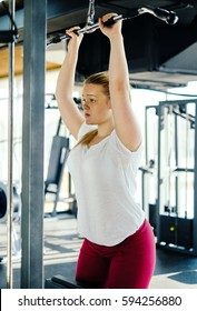 Sports young woman doing exercises in the gym on Lat Machine