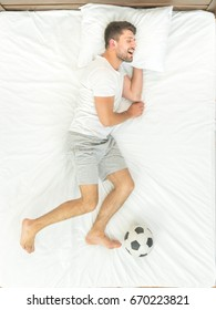 The sportsman with a ball sleeping on the bed. view from above