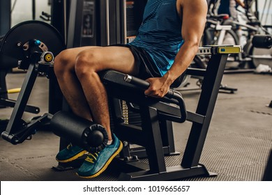 Sportsman with beautiful legs muscle doing leg press exercise.