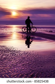 Sportsman with bicycle is near ocean