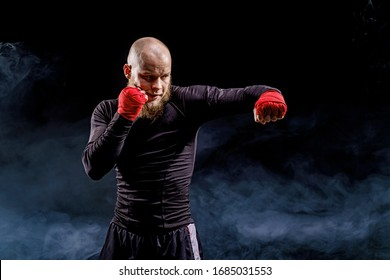Sportsman boxer fighting on black background with smoke. Boxing sport concept.