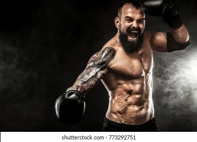 Sportsman boxer fighting on black background with smoke. Copy Space. Sport concept.