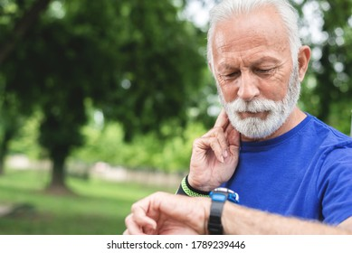 Sportsman checking watch while exercising outdoors at park