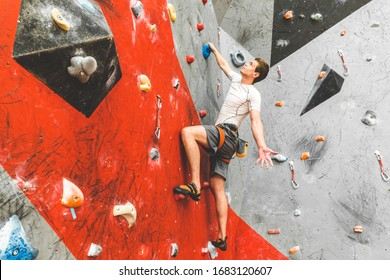 Sportsman climber moving up on steep rock, climbing on artificial wall indoors. Extreme sports and bouldering concept