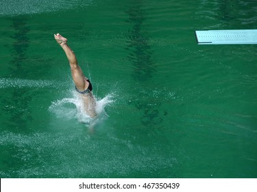 Sportsman diving in olympic swimming pool from a high-board
