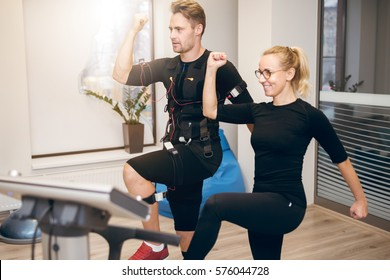 Sportsman doing ems training with personal trainer