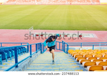 sportsman doing speed exercise for muscles on the stairs on the stadium