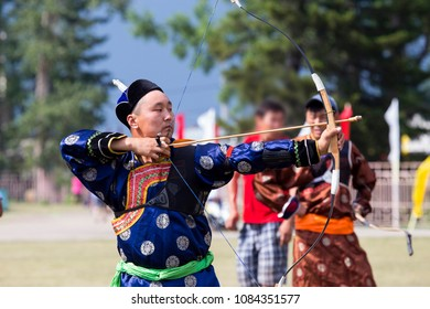 The sportsman is dressed in a traditional Buryat-Mongolian suit, shooting with his arrows during a national holiday.